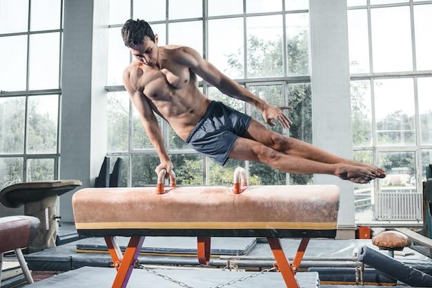 O esportista durante exercício difícil, ginástica esportiva Foto gratuita