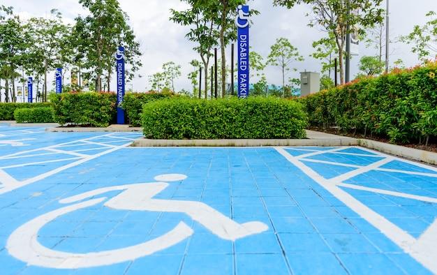 O estacionamento deficiente azul assina dentro a área do parque de estacionamento. Foto Premium