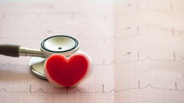 O estetoscópio ee a forma do coração pôr sobre o eletrocardiograma do relatório do papel. Foto Premium