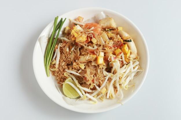 O estilo tailandês fritado isolado do macarronete com camarões e marisco tailândia chama a almofada tailandesa, estilo tailandês salteado do macarronete no branco. Foto Premium