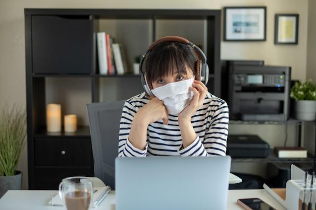 O estudante universitário usa máscara e trabalha com o computador em casa. ouvindo aula on-line. Foto Premium