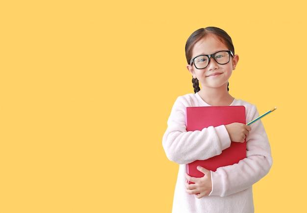 O eyeglass vestindo de sorriso da estudante abraça um livro e manter disponivel do lápis isolado sobre o amarelo. Foto Premium