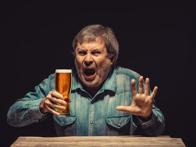 O fã encantado e emocional com um copo de cerveja Foto gratuita