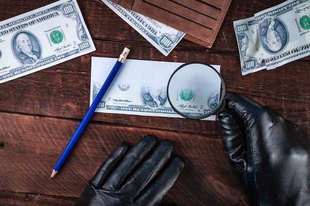 O falsificador em luvas pretas forja as notas. conceito falso. dinheiro falso, uma carteira com dólares americanos, uma lupa. vista do topo Foto Premium