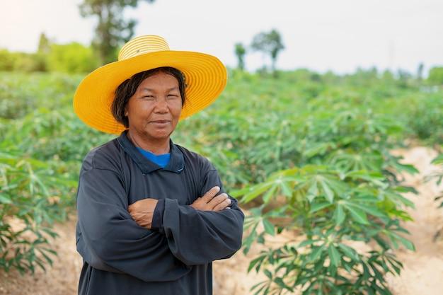O fazendeiro esperto da mulher cruzou seus braços com campo da mandioca. agricultura e conceito de sucesso fazendeiro inteligente Foto Premium