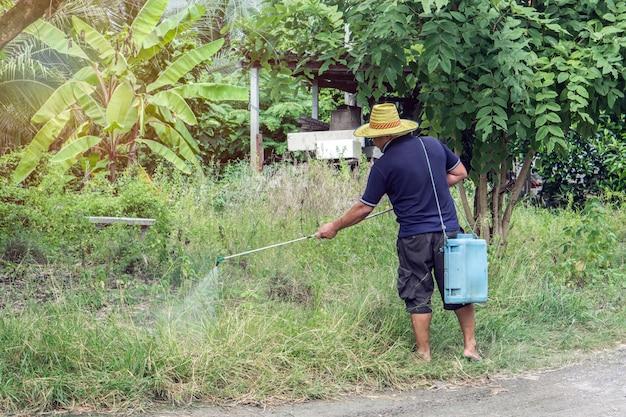 O fazendeiro mata a planta daninha que pulveriza pesticidas no campo pelo pulverizador manual. Foto Premium