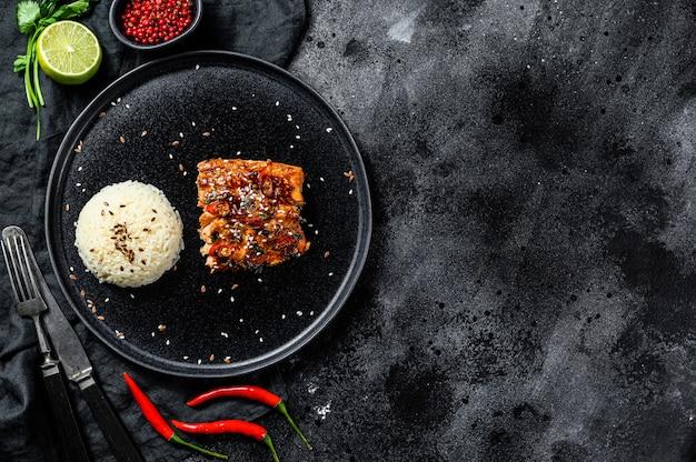 O filé de truta grelhada japonesa teriyaki vitrificado em molho delicioso com um prato de arroz. Foto Premium