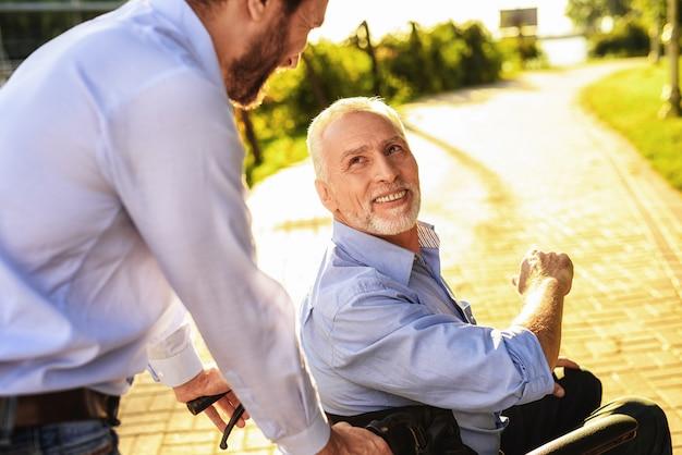 O filho leva o homem deficiente na cadeira de rodas. Foto Premium