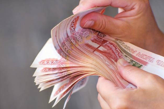 O financista segura um maço de notas na mão oferecendo empréstimos a juros e parcelados Foto Premium