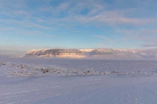 O fiorde coberto de gelo tempelfjorden, com a montanha templet e a pista de snowmobile em primeiro plano. svalbard, noruega. Foto Premium