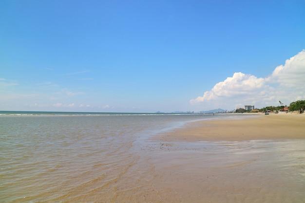 O foco suave das ondas bate na praia com areia e o céu azul com reflexão. Foto Premium