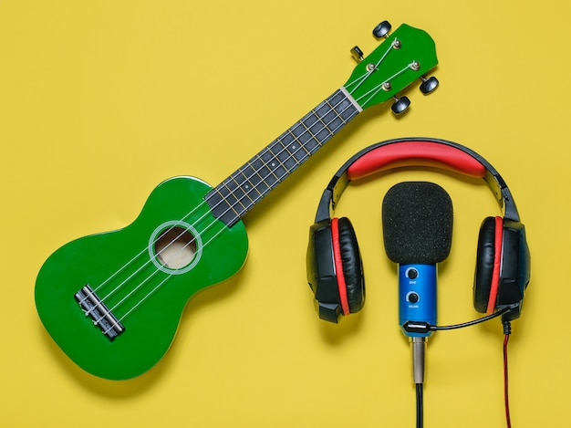 O fone de ouvido com fio azul com fio mic e ukulele de guitarra verde sobre um fundo amarelo. equipamento para gravação de faixas de música. a vista do topo. postura plana. Foto Premium