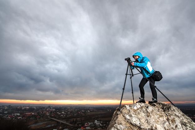 O fotógrafo está de pé com sua câmera no tripé na rocha grande no ponto de visão geral da cidade Foto Premium