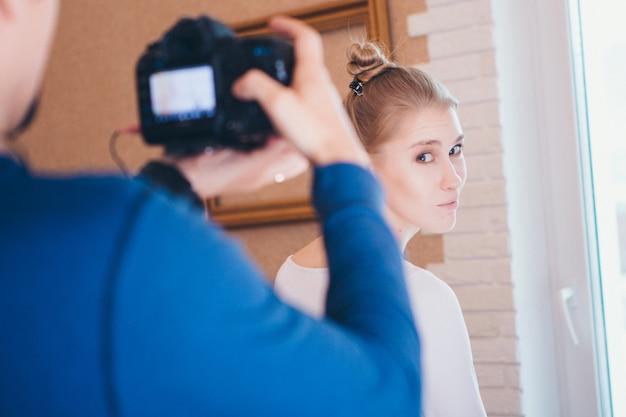 O fotógrafo leva uma bela modelo no estúdio. garota anuncia roupas. publicidade em foto e vídeo Foto Premium
