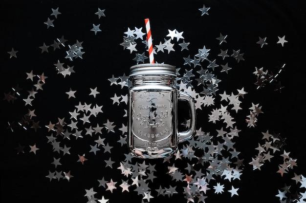 O frasco de pedreiro com estrela de prata polvilha confetes no fundo preto. fundo de natal Foto Premium