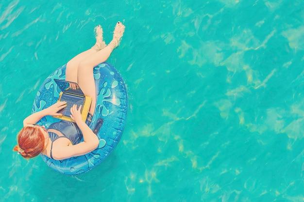O freelancer bonito novo da mulher está flutuando no mar ou na associação em um círculo da natação Foto Premium