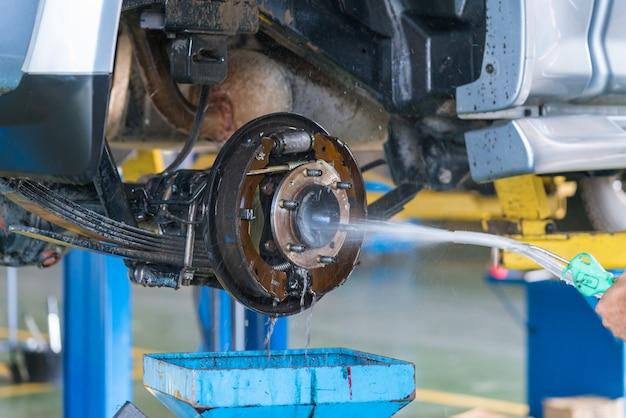 O freio de tambor de lavagem do trabalhador de um carro sob uma alta pressão. Foto Premium