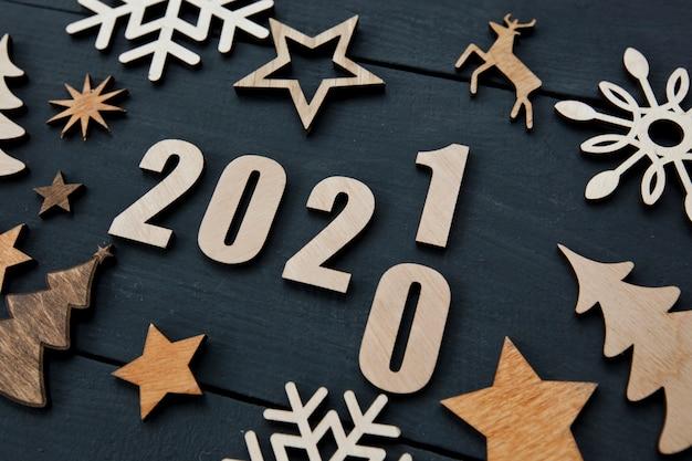 O fundo de natal bonito com muitas pequenas decorações de madeira e números de madeira 2021 na mesa de madeira. Foto Premium