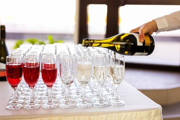 O garçom derrama champanhe em copos na rua - catering de casamento Foto Premium