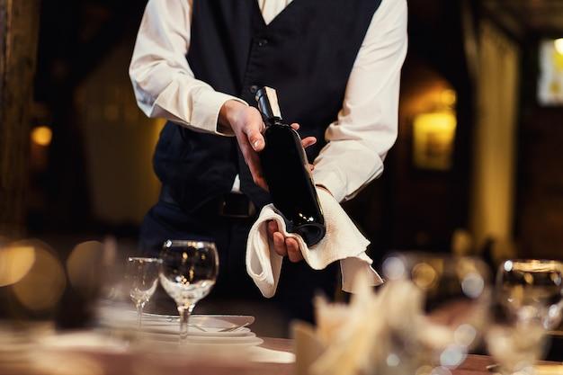 O garçom oferece aos visitantes vinho Foto Premium