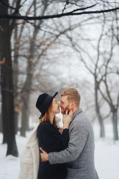 O garoto e a garota estão descansando na floresta de inverno. Foto gratuita