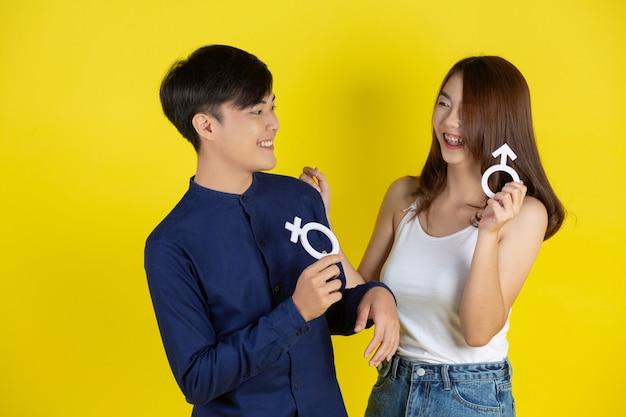 O garoto e a garota estão segurando o símbolo masculino e feminino na parede amarela Foto gratuita