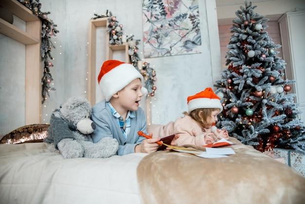 O garoto escreve para o papai noel. noite de natal em família. presentes de ano novo. sala luminosa decorada Foto Premium