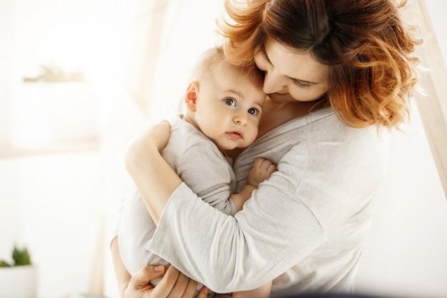 O garoto recém-nascido fofo olha assustadoramente para o lado, enquanto a jovem mãe bonita abraça suavemente o bebê, expressando seu amor e apoio. conceito de família Foto gratuita