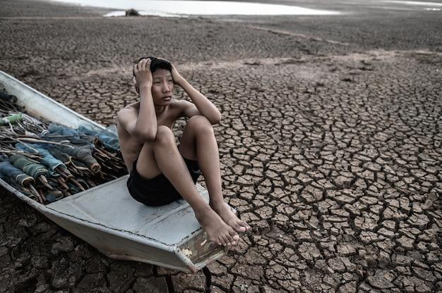 O garoto sentou-se em um barco de pesca e pegou a cabeça em solo seco, aquecimento global Foto gratuita