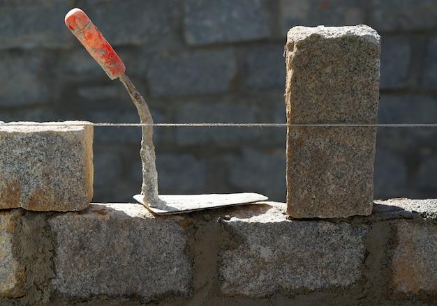 O granito bloqueia a construção da parede com argamassa Foto Premium
