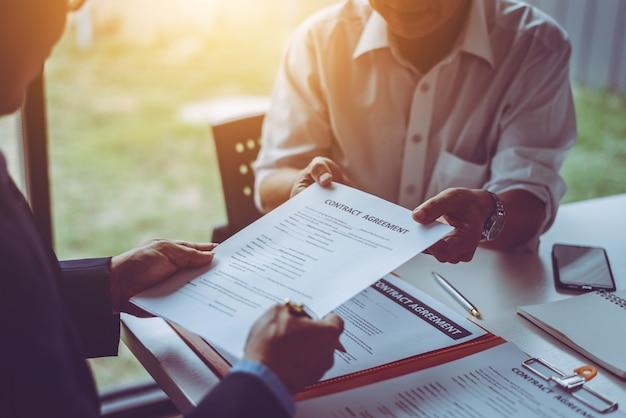 O grupo de executivos asiáticos e de advogados da idade média que discutem e assinam um contrato. Foto Premium