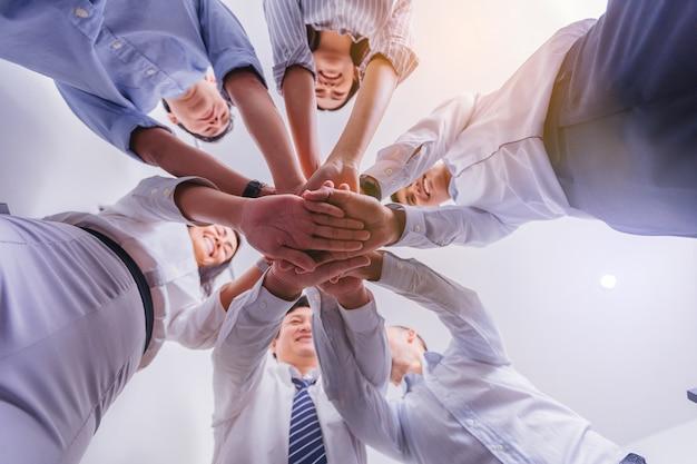 O grupo de executivos junta as mãos no escritório. visão de baixo ângulo. Foto Premium