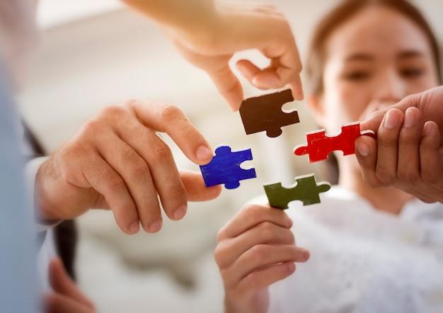 O grupo de executivos que montam o enigma de serra de vaivém e representa o apoio da equipe e ajuda junto. Foto Premium