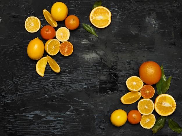 O grupo de frutas frescas - limões e tangerinas contra o espaço negro Foto gratuita