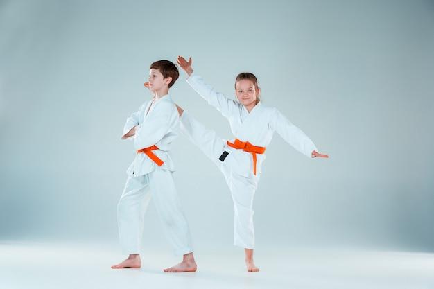 O grupo de meninos e meninas no treinamento de aikido na escola de artes marciais. estilo de vida saudável e conceito de esportes Foto gratuita