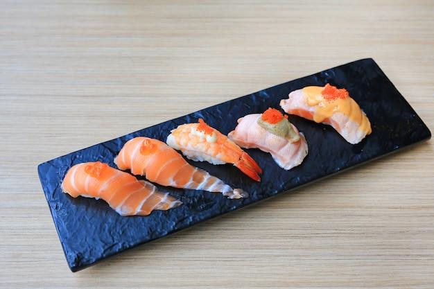 O grupo do marisco do sushi serviu na placa de pedra preta na tabela de madeira. cozinha japonesa. Foto Premium