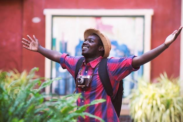 O homem africano do turista sente feliz com lugar do curso na cidade do cenário. Foto Premium