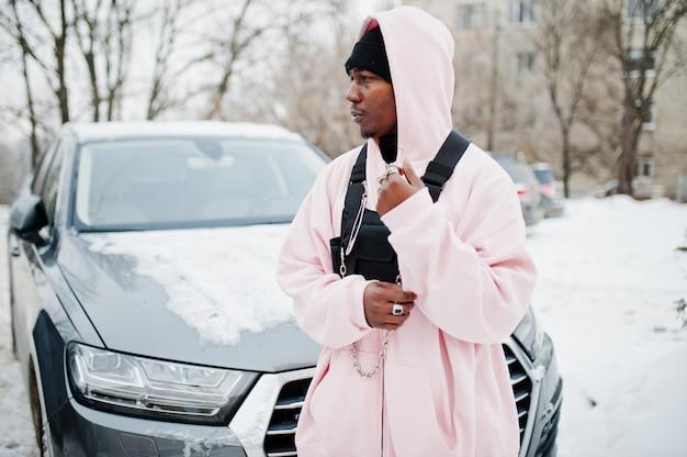 O homem afro-americano do estilo urbano à moda no hoodie cor-de-rosa levantou contra o carro do suv no inverno. rapper afro. Foto Premium