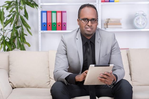 O homem afro-americano está usando a tabuleta digital em casa. Foto Premium