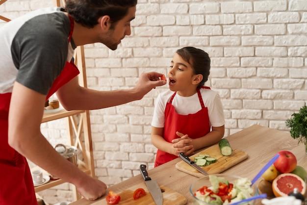 O homem árabe está alimentando a filha pequena com tomate. Foto Premium