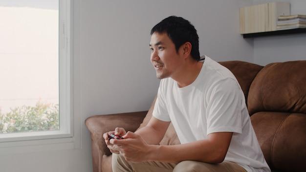 O homem asiático novo que usa o manche que joga os jogos video na televisão na sala de visitas, sentimento masculino feliz usando relaxa o tempo que encontra-se no sofá em casa. os homens jogam jogos relaxam em casa. Foto gratuita