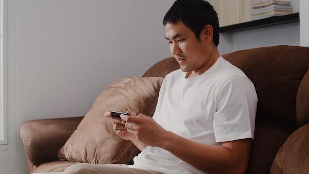 O homem asiático novo que usa o telefone celular que joga videogames na televisão na sala de visitas, sentimento masculino feliz usando relaxa o tempo que encontra-se no sofá em casa. os homens jogam jogos relaxam em casa. Foto gratuita