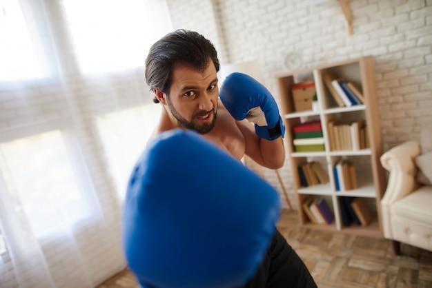 O homem atlético considerável em luvas de encaixotamento faz o perfurador. Foto Premium