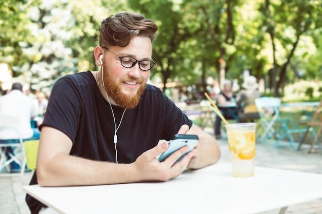 O homem atrativo do ruivo com uma barba escuta a música em um telefone celular ao sentar-se em uma tabela do café. Foto Premium