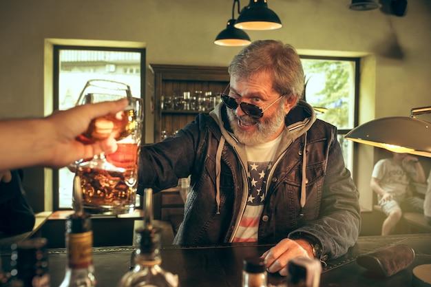 O homem barbudo sênior bebendo cerveja no pub Foto gratuita