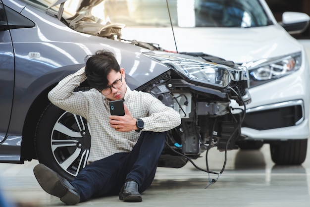 O homem bonito fez um gesto estressante depois que o carro danificado foi atingido por um acidente e usou o telefone para pedir ajuda depois que o carro bateu na estrada - o carro tem seguro contra acidentes. Foto Premium