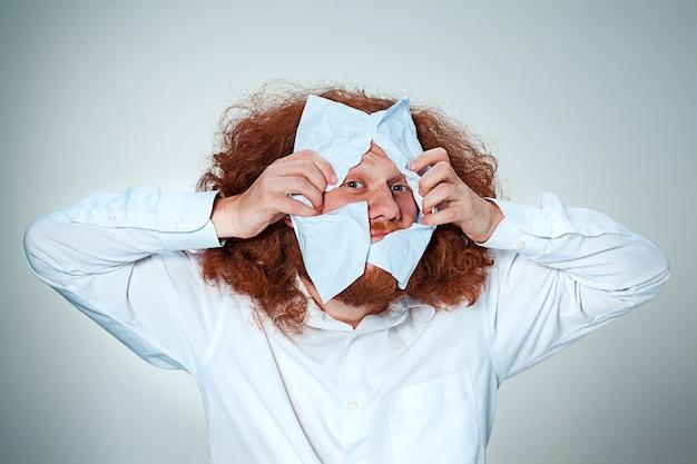 O homem bravo rasgando papel em cinza Foto gratuita