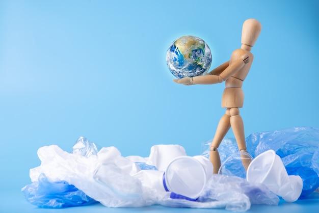 O homem carrega o planeta nas mãos para salvar a terra do lixo e do plástico. elementos fornecidos pela nasa Foto Premium