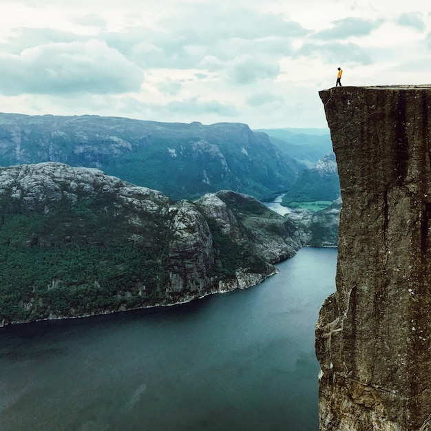 O homem com jaqueta amarela coloca no topo da rocha Foto gratuita