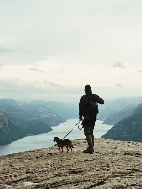 O homem com um cachorro está parado antes da bela paisagem Foto gratuita